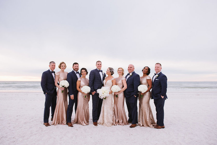 St. Pete Beach Bridal Party Wedding Portrait with Bridesmaids in Gold Sequin Gowns, Groomsmen in Navy Blue Suits with Bowties and Bride in Ivory Lace Martina Liana Gown   St. Petersburg Wedding Venue The Don CeSar   Tampa Bay Wedding Photographer Jonathan Fanning Studio and Gallery