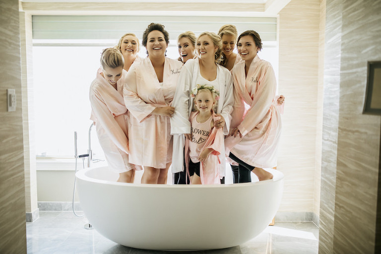Bridal Party Getting Ready Wedding Portrait with Bride and Bridesmaids with Flower Girl in Pink and White Robes in Bathtub | Getting Ready Suite at Ritz Carlton Sarasota | Tampa Bay Wedding Planner NK Productions