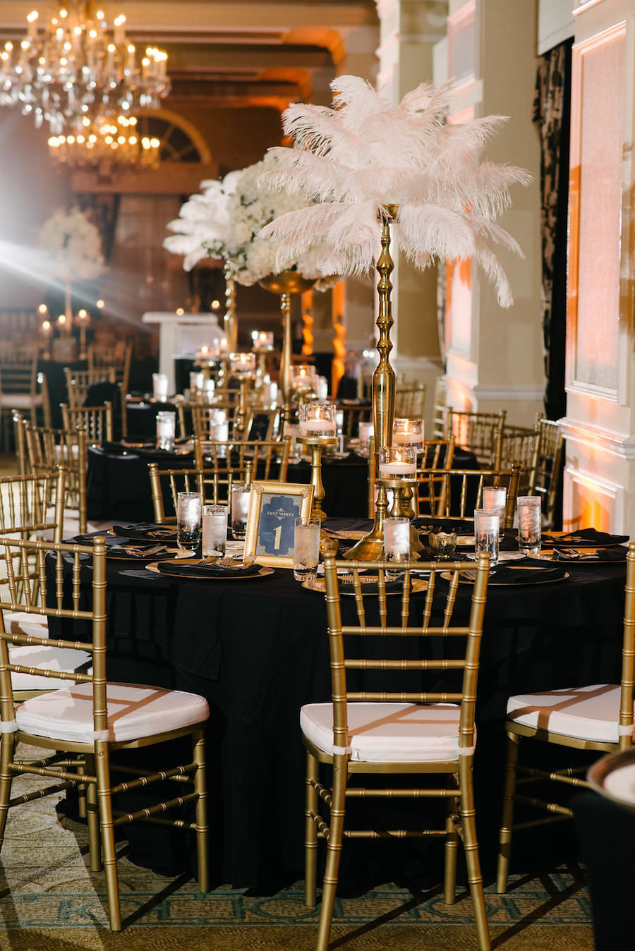 Ivory, Black and Gold Wedding Reception with Tall White Feather Centerpieces and Gold Chiavari Chairs with Black Linens   St. Petersburg Wedding Venue The Don CeSar   Tampa Bay Wedding Photographer Jonathan Fanning Studio and Gallery   A Chair Affair