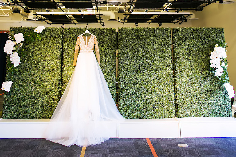 Nude Illusion Lace Wedding Dress with Sleeves and Greenery Hedge Backdrop Wall | Tampa Bay Bridal Shop Isabel O'Neil Bridal | Rental and Decor Company A Chair Affair | Wedding Photographer Limelight Photography