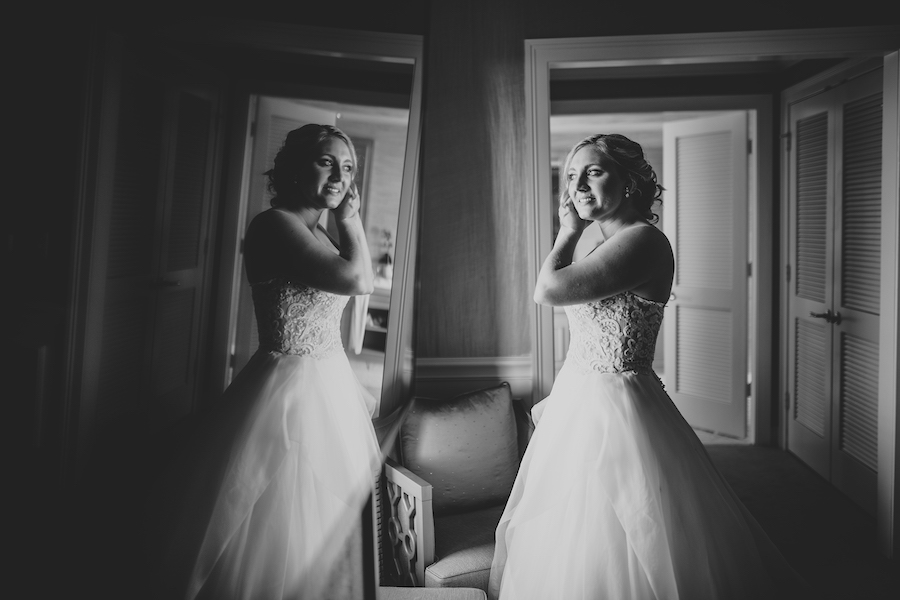 Bride Getting Ready Putting on Earrings in Mirror in Reem Acra Ballgown   Getting Ready Suite at Ritz Carlton Sarasota   Tampa Bay Wedding Planner NK Productions