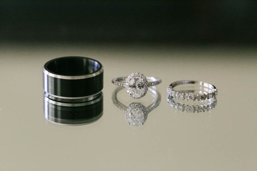Black and Silver Titanium Wedding Band and Diamond Engagement Ring and Wedding Band on Mirror Table   Tampa Bay Wedding Videographer Hatfield Productions