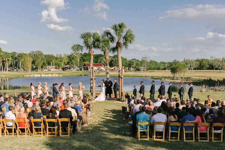 Blush Pink Rustic Lakefront Wedding Ceremony with Bride and Groom at Altar with Bridal Party | Tampa Bay Wedding Videographer Hatfield Productions