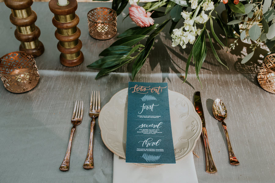 Vintage Place Setting with Gold Silverware and Green Menu Card   Peach and Blush Pink Wedding Centerpieces with Greenery, Candles and Wicker Chairs   Retro Vintage Boho Wedding Inspiration   Tampa Wedding Florist Northside Florist   Planner Glitz Events   Outdoor Venue Casa Lantana