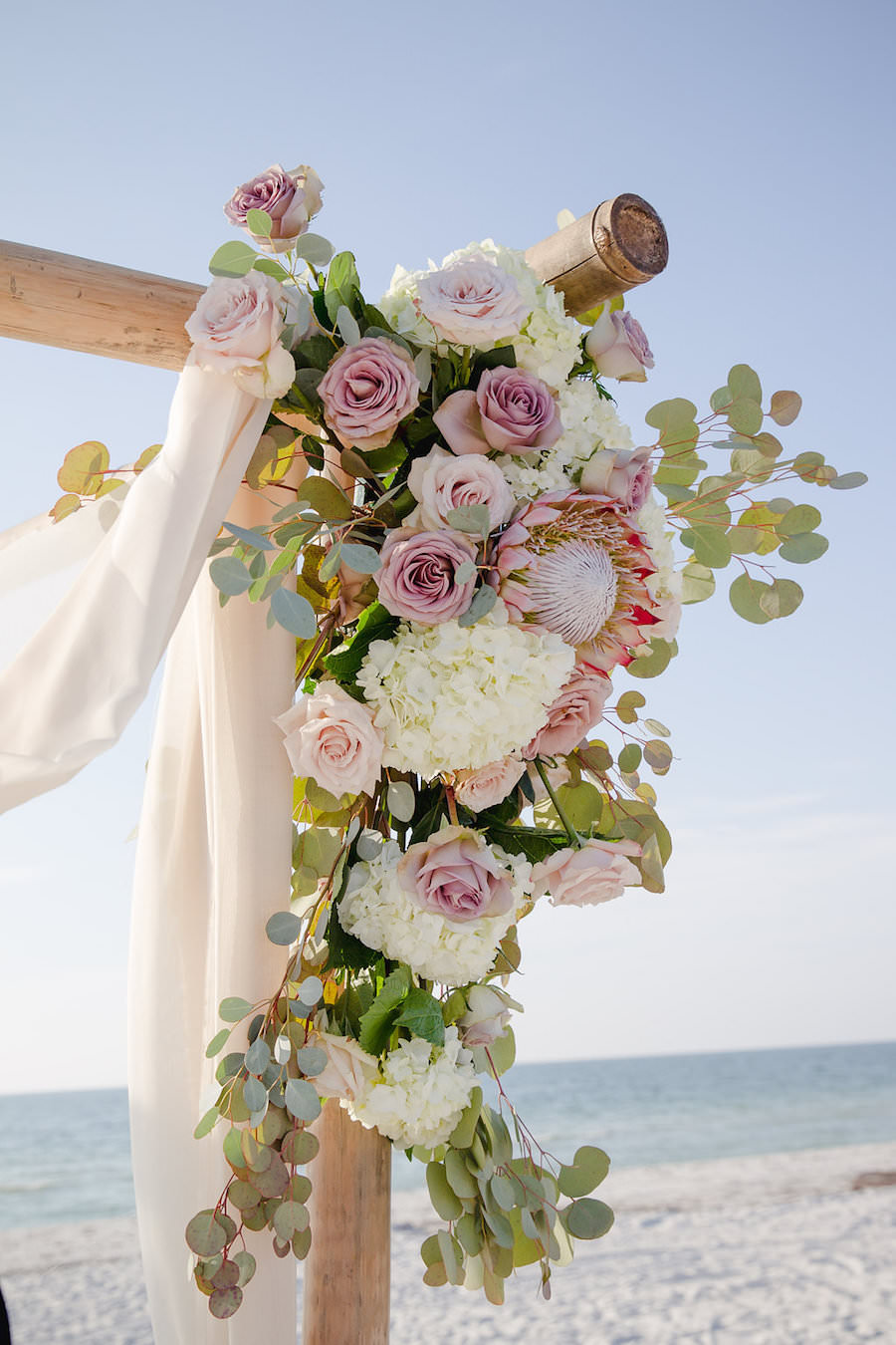 White and Blush Pink Dusty Rose Wedding Ceremony Floral Arrangement with White Ivory Hydrangeas with Greenery on Wooden Altar with Draping | Clearwater Beach Wedding Planner Parties a la Carte