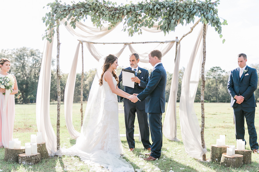 Draped Wedding Altar with Greenery Decor and Tree Stumps with Candles   Outdoor Wedding Ceremony at Tampa Bay Wedding Venue Orange Blossom Barn   Rustic, Country Wedding Inspiration