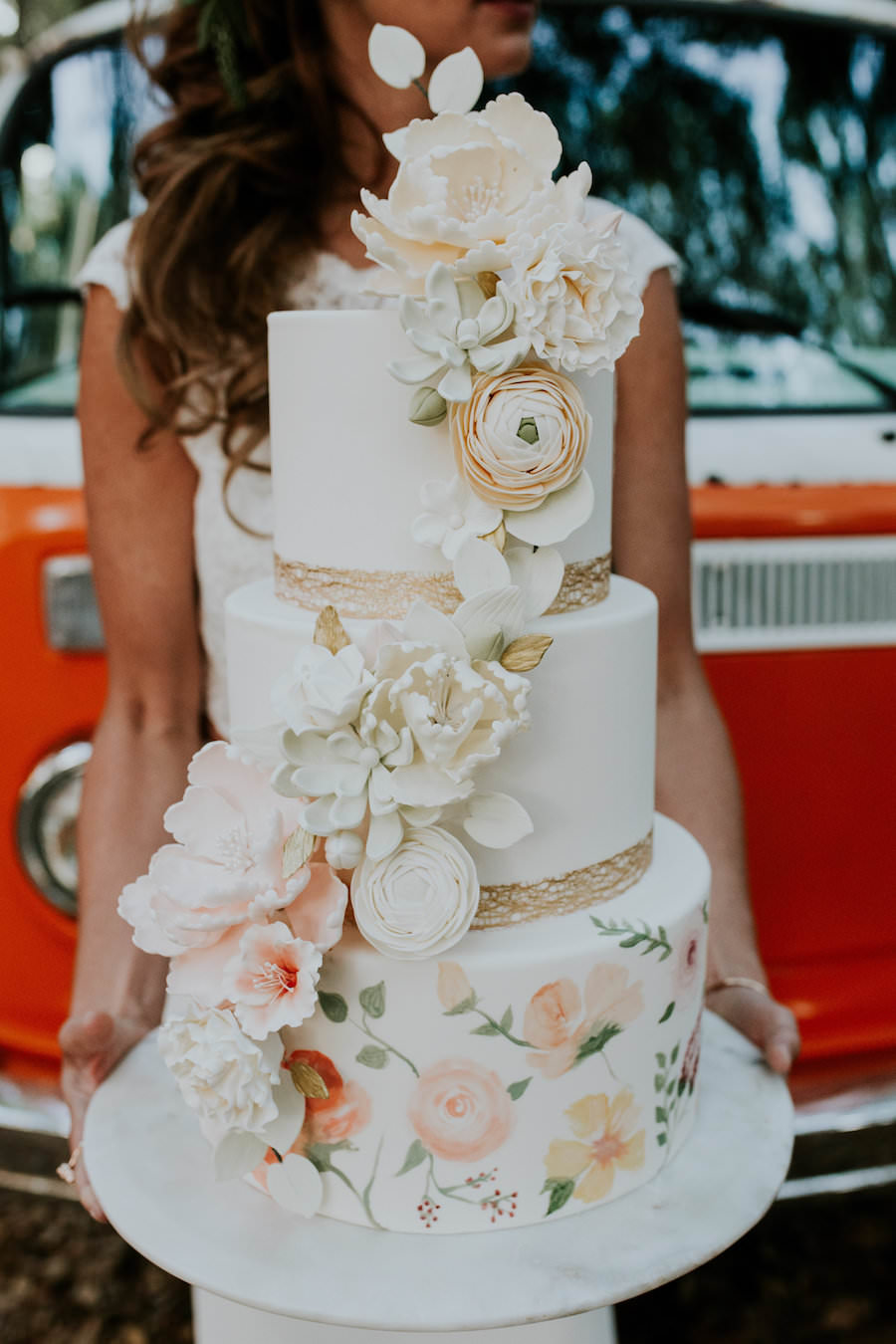 Bride Holding 3-Tier Round Hand Painted Wedding Cake with Cascading Sugar Flowers and Gold Leaf Boarder   Retro Vintage Boho Wedding Inspiration with Orange VW Bus   Tampa Wedding Cake Bakery Hands on Sweets