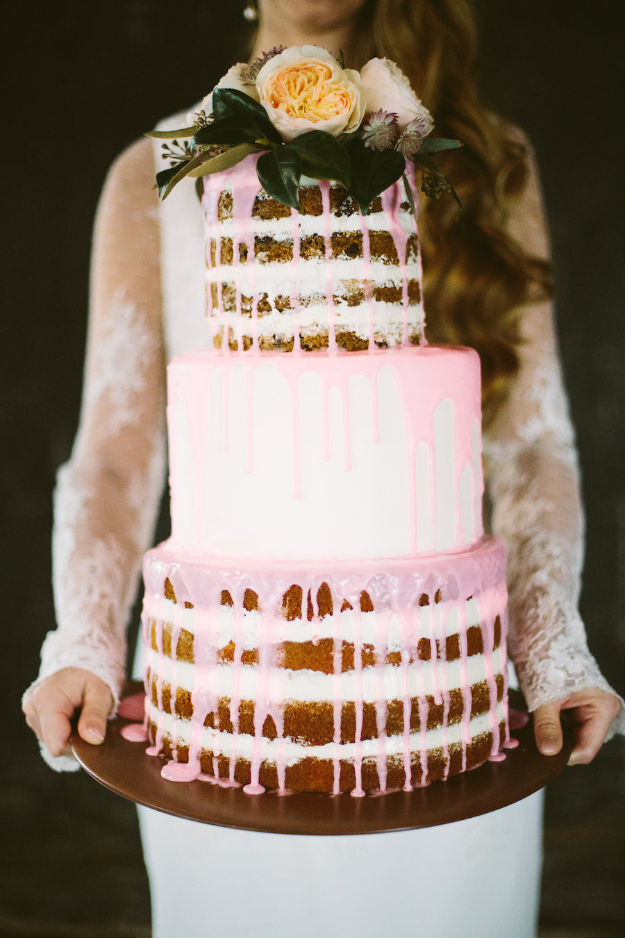Bride in Long Sleeve Lace Isabel O'Neil Bridal Collection Wedding Dress Holding Three Tiered Round Naked Wedding Cake with Dripping Pink Icing and Fresh Rose Floral Cake Topper | Tampa Bay Wedding Planner Isabel O'Neil Bridal Collection