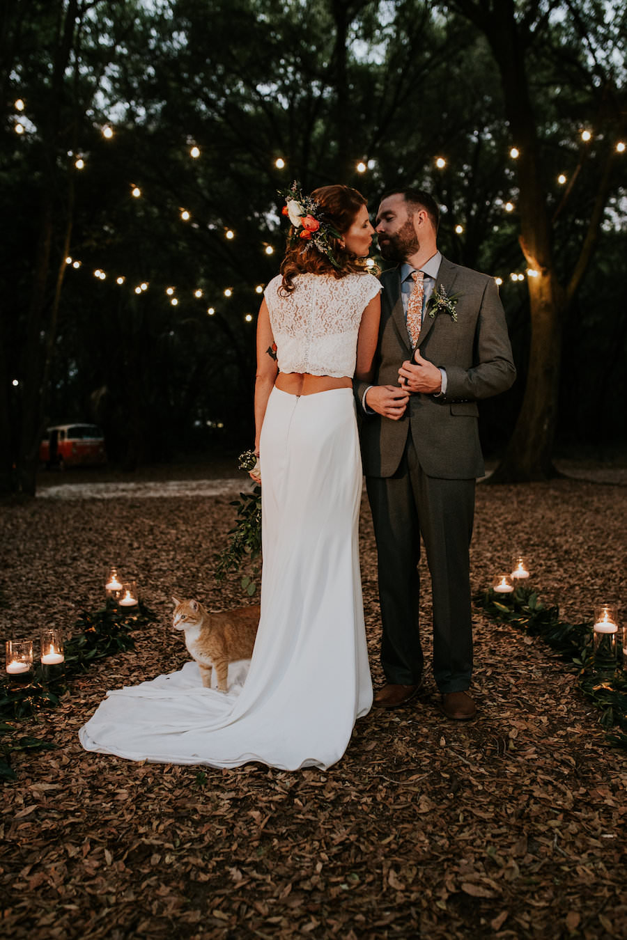 Bride and Groom Wedding Portrait with in Forest with Market String Lights and Orange Cat   Retro Vintage Boho Wedding Inspiration   Planner Glitz Events   Outdoor Venue Casa Lantana   Lighting by Gabro Event Services
