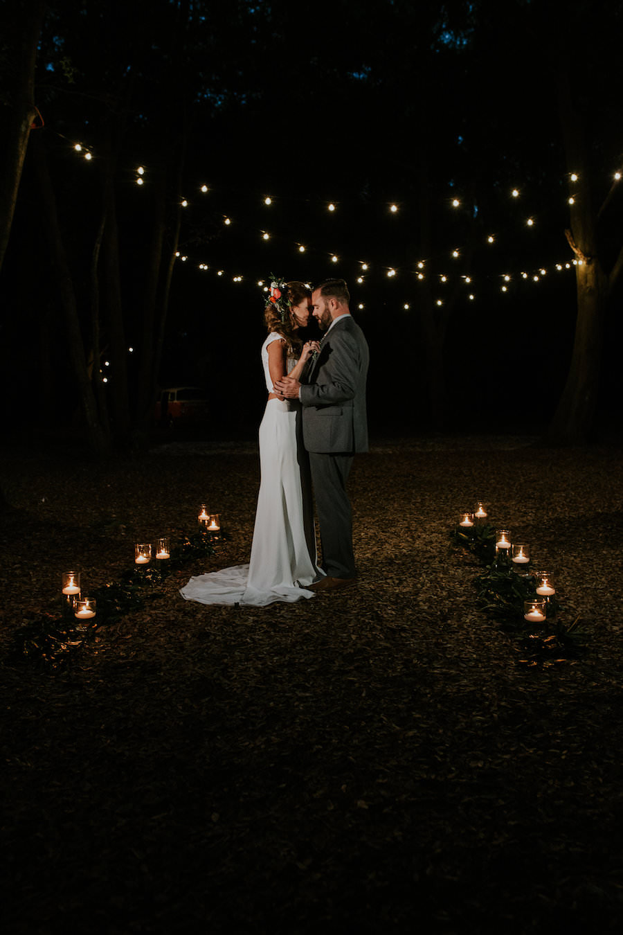 Bride and Groom Wedding Portrait with in Forest with Market String Lights   Retro Vintage Boho Wedding Inspiration   Planner Glitz Events   Outdoor Venue Casa Lantana   Lighting by Gabro Event Services