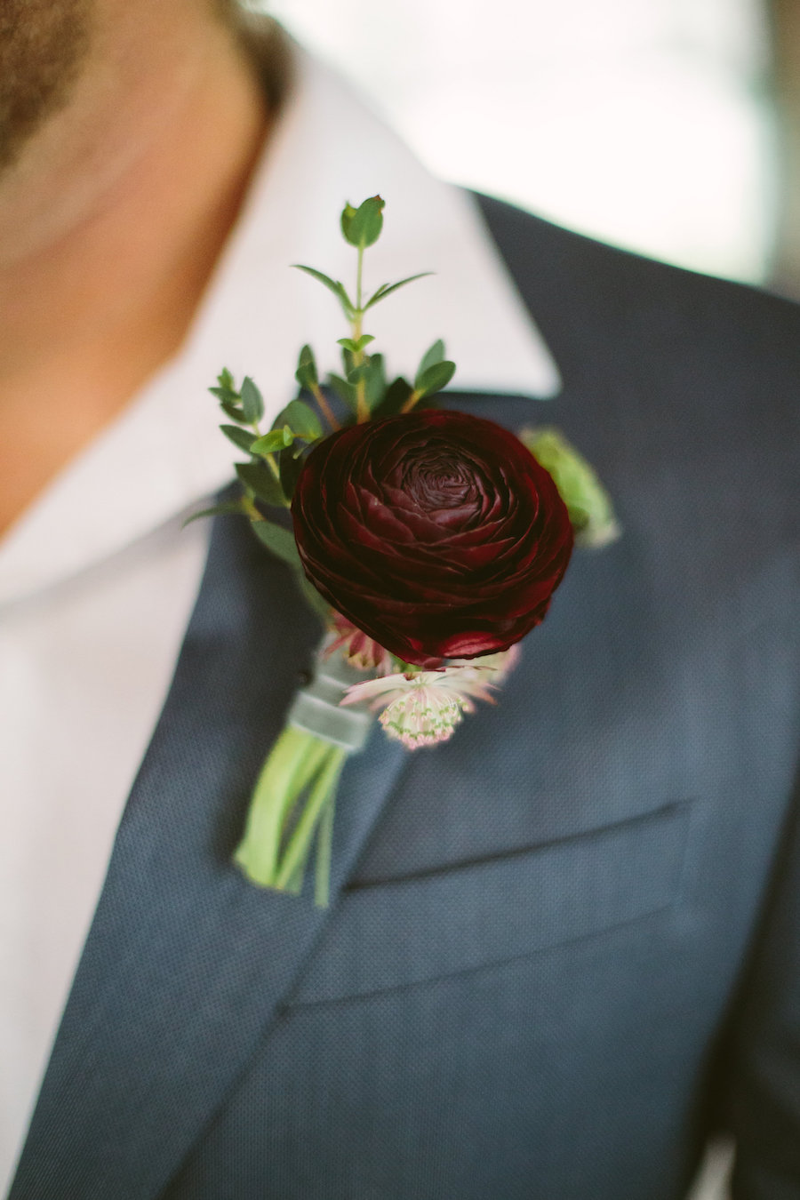 Modern Groom's Wine Colored Rose with Greenery Boutonnière on Grey Suit with White Button Down Shirt | Groom in Grey Suit Boutonnière Portrait