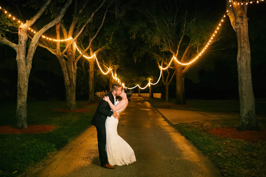 Outdoor Nighttime Bride and Groom Kissing Wedding Portrait Between Trees Lined with String Lights   Tampa Bay Wedding Videographer Hatfield Productions