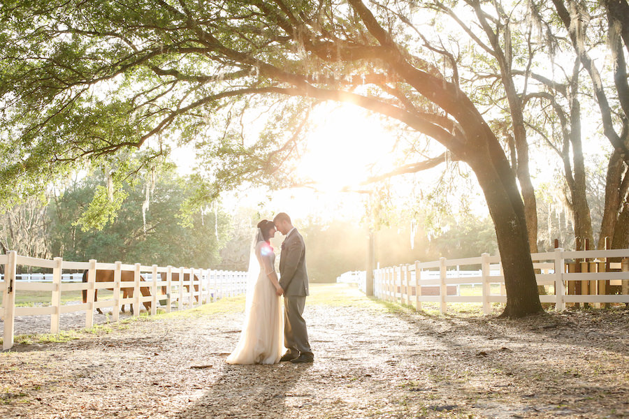 Bride and Groom Rustic Outdoor Wedding Portrait at Tampa Bay Wedding Venue The Lange Farm with White Picket Fence and Horses