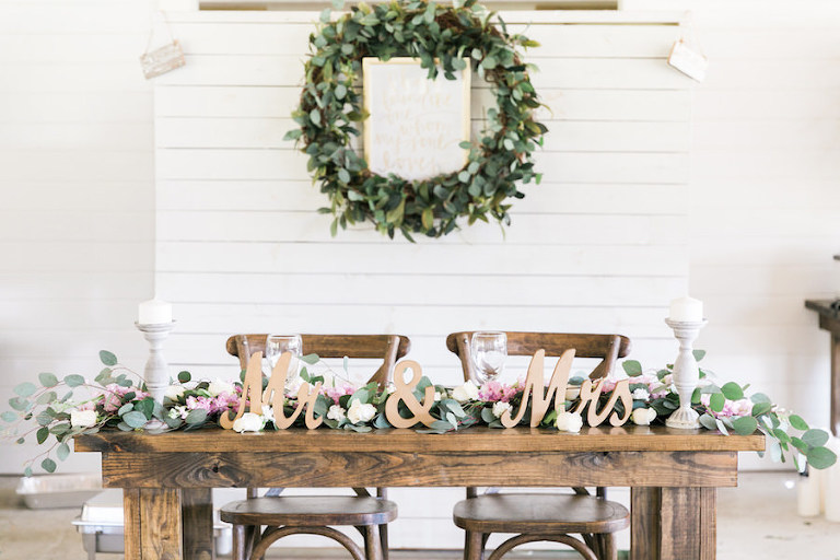Bride and Groom Sweetheart Table with Wooden Farm Table with Mr. and Mrs. Sign and Table Garland | Greenery Plant Wedding Wreath Decor with Wedding Sign | Rustic, Country Wedding Inspiration | Tampa Bay Wedding Reception | Florist Cotton & Magnolia