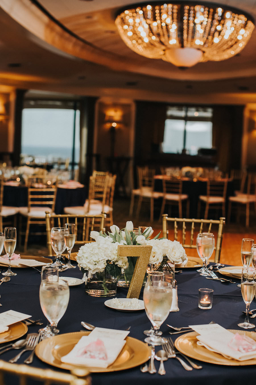 Elegant Gold Wedding Reception with Navy Blue Linens and Gold Chiavari Chairs, Beaded Charger Plates, Low White Tulip Centerpieces and Gold Glitter Table Numbers | Wedding Reception Decor Inspiration and Ideas | Downtown Tampa Wedding Reception Venue The Tampa Club