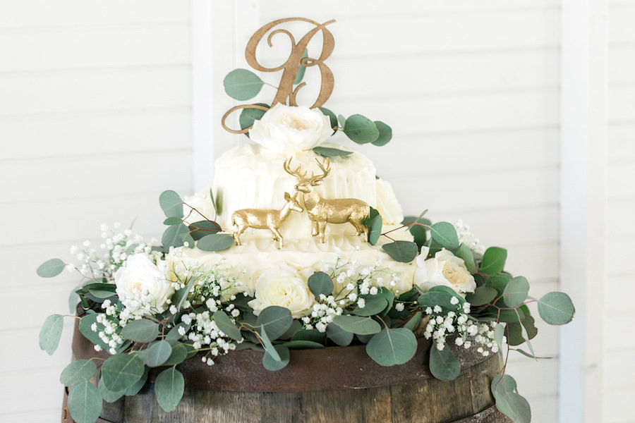White Buttercream Wedding Cake with Wooden Initial Cake Topper and Hunting Deer on Oak Wooden Barrel   Rustic, Country Wedding Reception Decor Inspiration