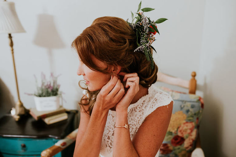 Bride Getting Ready Putting on Jewelry with Flowers in Hair | Retro Vintage Boho Wedding Inspiration | Tampa Wedding Florist Northside Florist