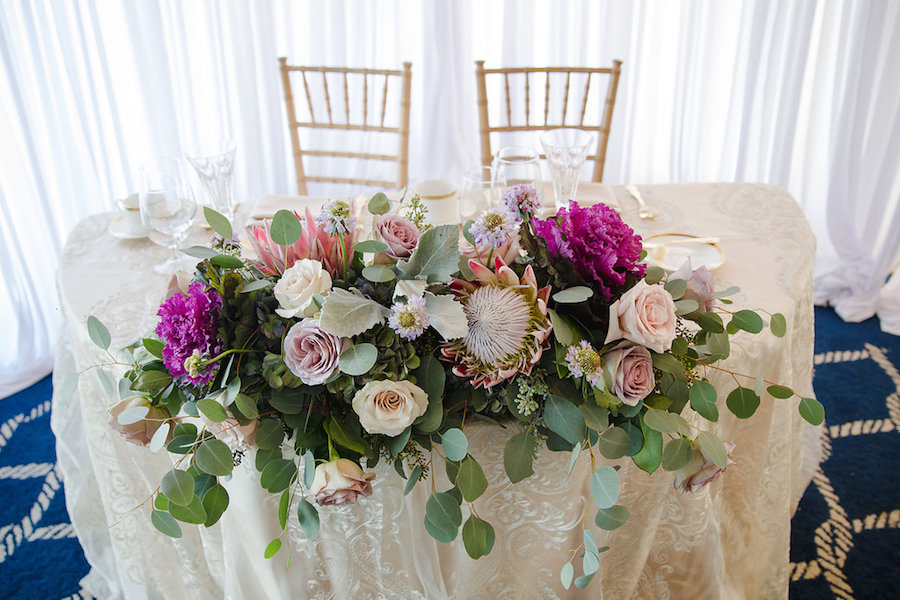 Dusty Pink Rose and Bright Pink, Purple, Fuschia Sweetheart Table Flowers with Greenery | Elegant Traditional Gold Wedding Reception Decor | Clearwater Beach Wedding Planner Parties a la Carte