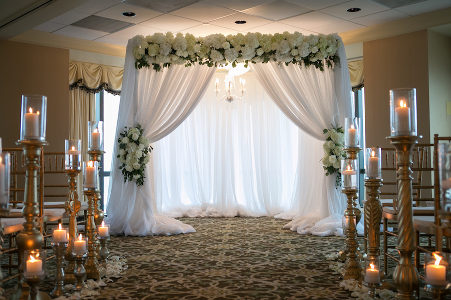 Wedding Ceremony: White Linen Arch with Ivory Florals and Chandelier   Tampa Bay Photographer Carrie Wildes Photography   Modern Elegant Downtown Tampa Wedding Venue The Tampa Club   Lighting and Linens Gabro Event Services   Wedding Florist Northside Florist