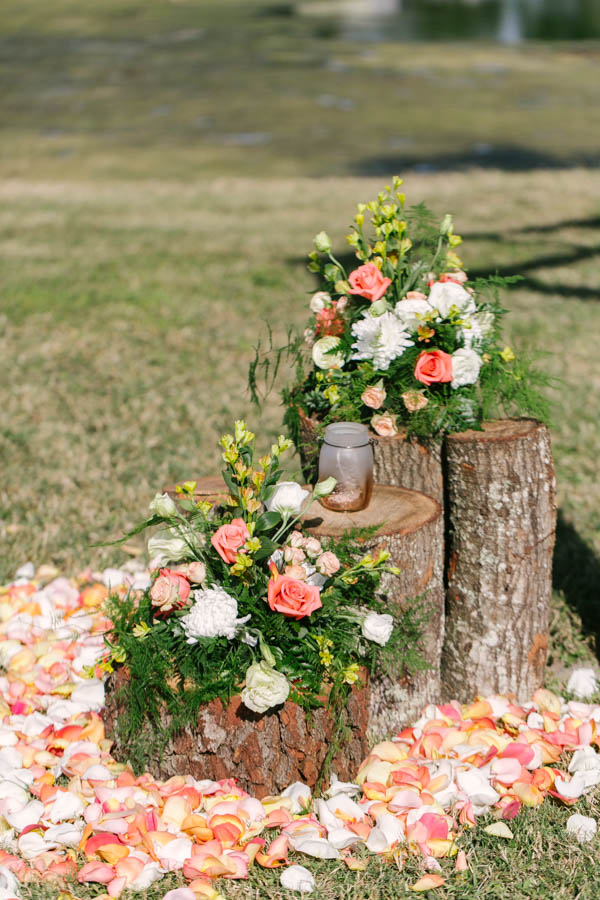 Ivory and Peach Rustic Floral Wedding Ceremony Decor on Tree Stumps with Rose Petals   Tampa Bay Wedding Videographer Hatfield Productions