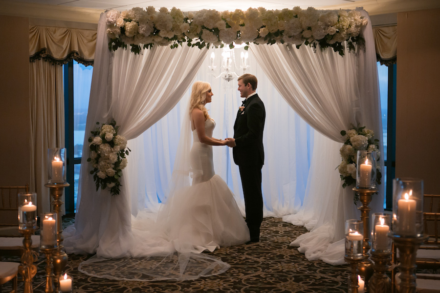 Wedding Ceremony: Bride and Groom at White Linen Arch with Ivory Florals and Chandelier   Tampa Bay Photographer Carrie Wildes Photography   Modern Elegant Downtown Tampa Wedding Venue The Tampa Club   Lighting and Linens Gabro Event Services   Wedding Florist Northside Florist