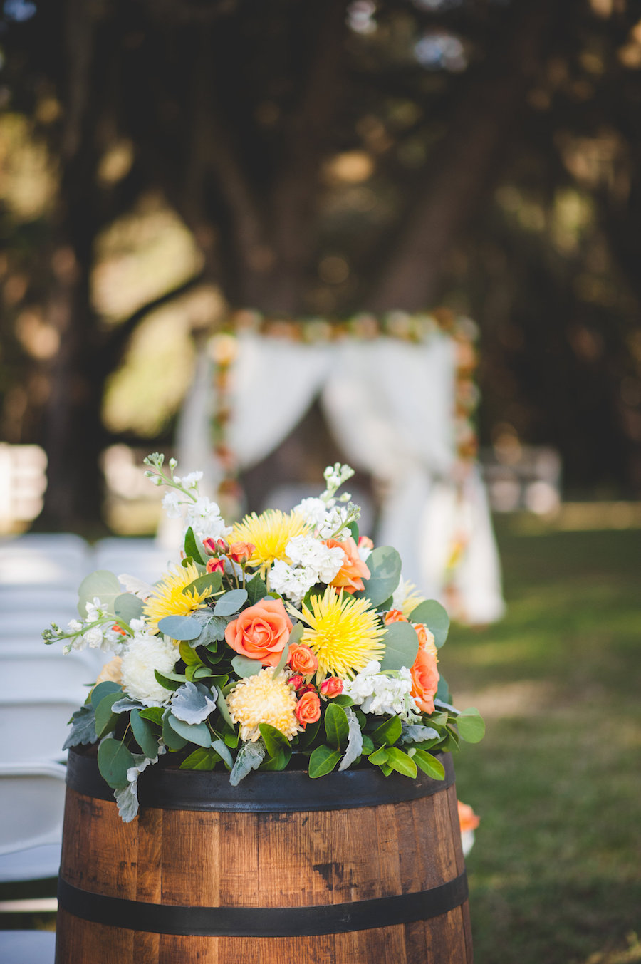 Fall Inspired Wedding Ceremony Floral Decor with Orange, Yellow Flowers, Greenery Accents and Wine Barrels