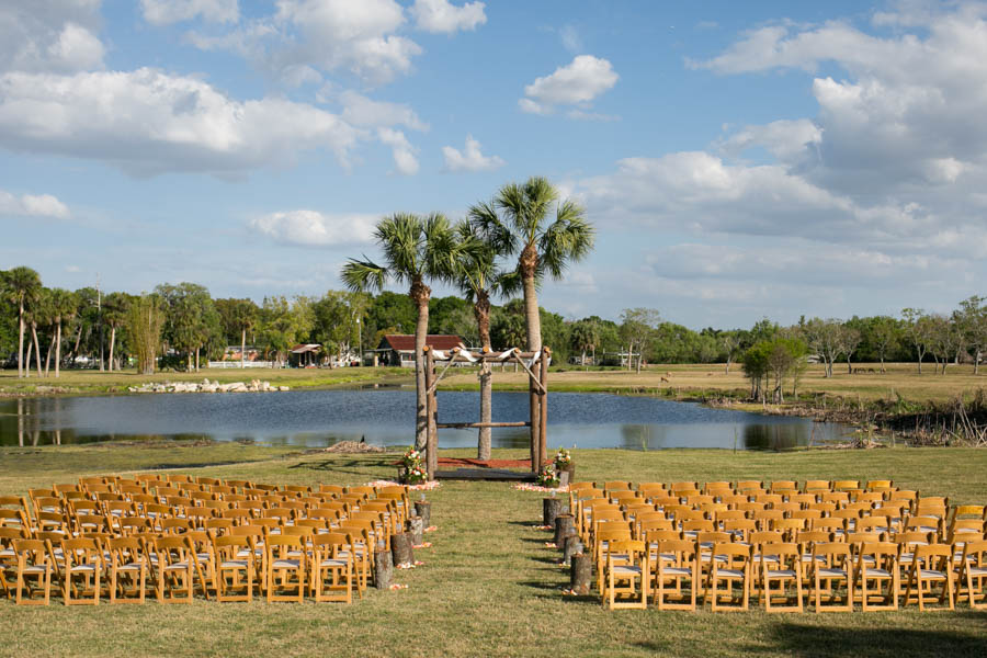 Rustic Lakefront Wedding Ceremony with Wooden Arch, Tree Stumps and Rose Petals   Tampa Bay Wedding Videographer Hatfield Productions