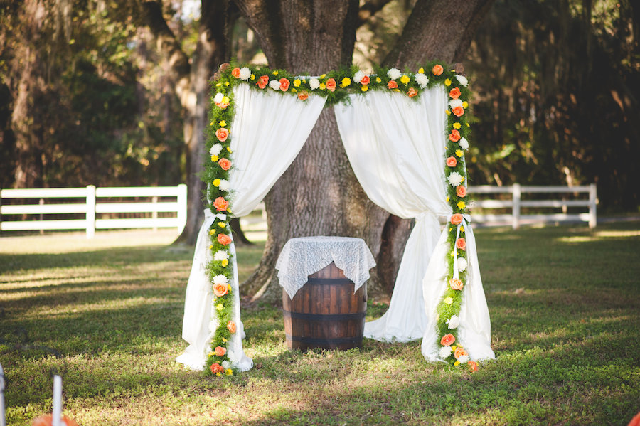 Outdoor Dade City Rustic Fall Inspired Wedding Ceremony Floral Arch Decor with Orange, Yellow Flowers, Greenery Accents, Wine Barrels and Soft Fabric Draping | The Lange Farm Wedding