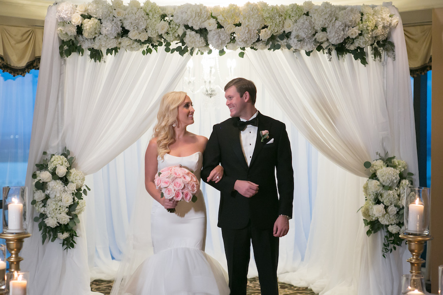 Wedding Ceremony Exit: Bride and Groom at White Linen Arch with Ivory Florals and Chandelier   Tampa Bay Photographer Carrie Wildes Photography   Modern Elegant Downtown Tampa Wedding Venue The Tampa Club   Lighting and Linens Gabro Event Services   Wedding Florist Northside Florist