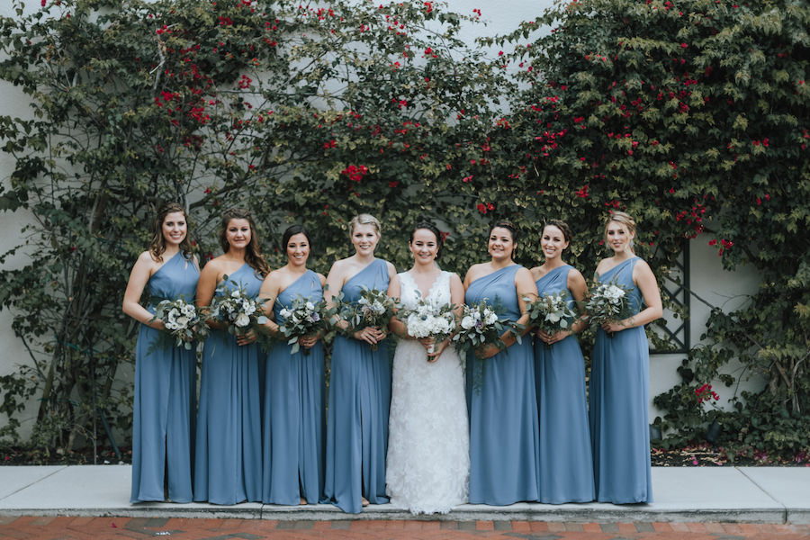 Bridal Wedding Portrait in Sleeveless Ivory Lace Wedding Dress and Bridesmaids in Dusty Blue One Shoulder Floor Length Bridesmaids Dress | Ivory, Purple and Greenery Wedding Bouquets with Eucalyptus | Tampa Bay Wedding Florist Wonderland Floral Art |Tampa Bay Wedding Videographer Bonnie Newman Creative