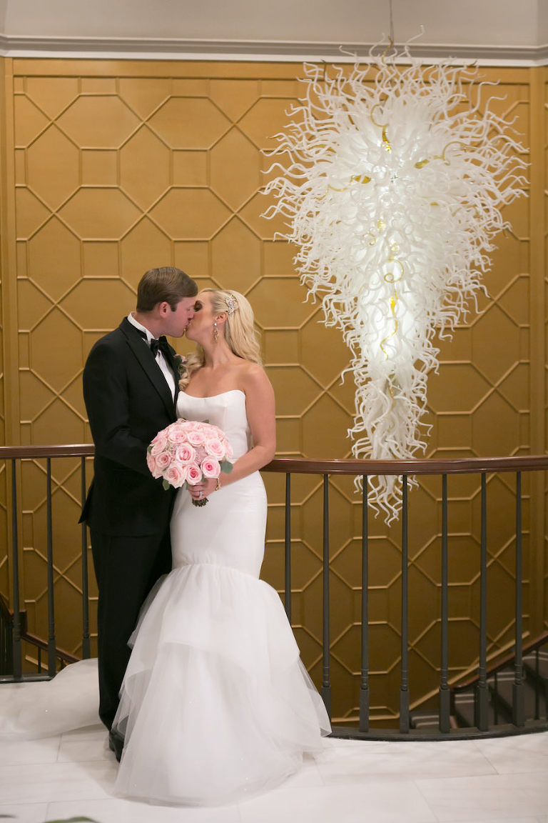 Bride and Groom Kiss Wedding Portrait by Modern White Chandelier with Pink Rose Bouquet | Elegant Downtown Tampa Wedding Venue The Tampa Club | Tampa Bay Wedding Photographer Carrie Wildes Photography | Wedding Florist Northside Florist