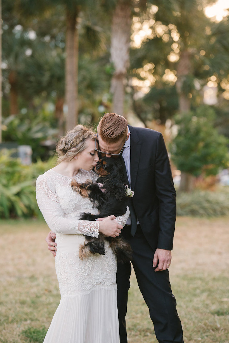Bride and Groom Florida Wedding Portrait with Puppy in Long Sleeve Lace Wedding Dress with Lace Veil and Groom in Tuxedo