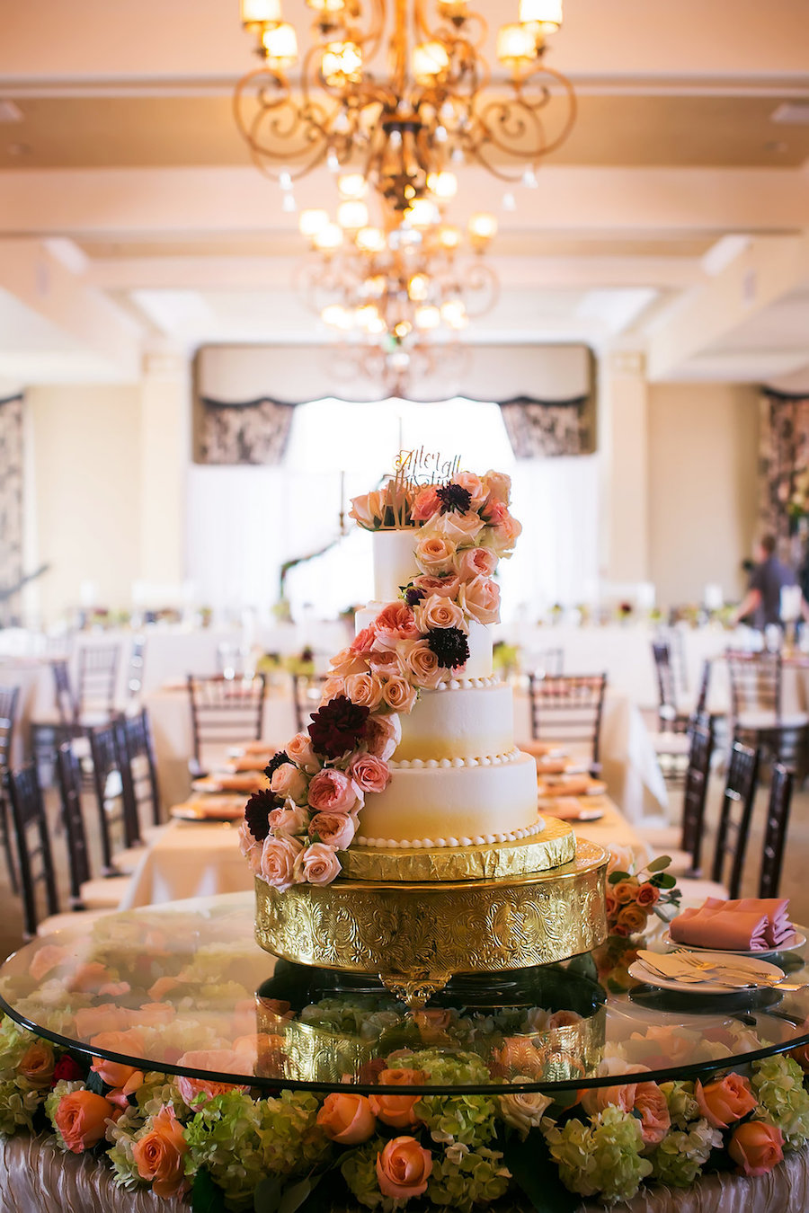 Four Tiered Round Ombre Wedding Cake with Fresh Rose Garland Accent Over Cake Table with Floral Decor in Don CeSar Hotel Ballroom   Limelight Photography