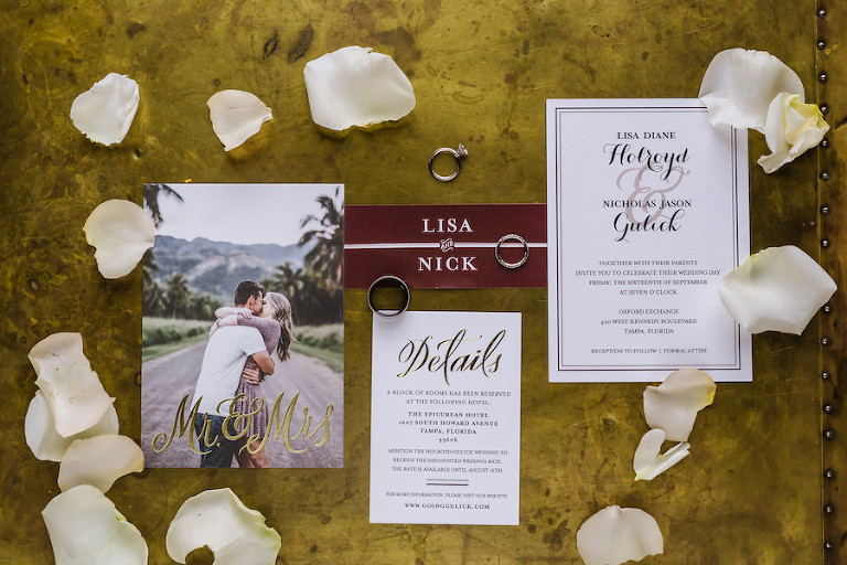 Stylish and Elegant White and Burgundy Bordeaux Wedding Invitation Suite Detail Photo with Rose Petals and Wedding Engagement Rings and Bands
