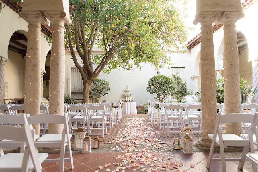 Wedding Ceremony Decor White Folding Chairs, Bush Rose Petals in the Aisle, and Gold Accent Lighting | Modern and Elegant Wedding Ceremony | Downtown St. Pete Unique Wedding Venue Museum of Fine Arts St Pete