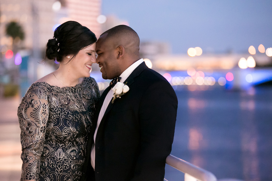 Wedding Couple Portrait of Classic Navy and Gold Wedding with with Bride wearing Embroidered Vintage Inspired Lace Dress by Tadashi Shoji and White Rose boutonniere   Downtown Waterfront Tampa Bay Wedding   Photographer Carrie Wildes Photography