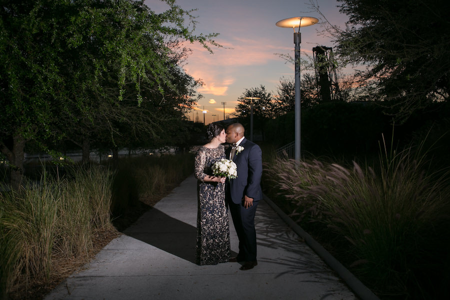 Nighttime Outdoor Couple Portrait of Classic Navy and Gold Wedding with with Bride wearing Embroidered Vintage Inspired Lace Dress by Tadashi Shoji and White Rose and Greenery Boutonniere and Bouquet   Northside Florist   Tampa Bay Wedding Photographer Carrie Wildes Photography