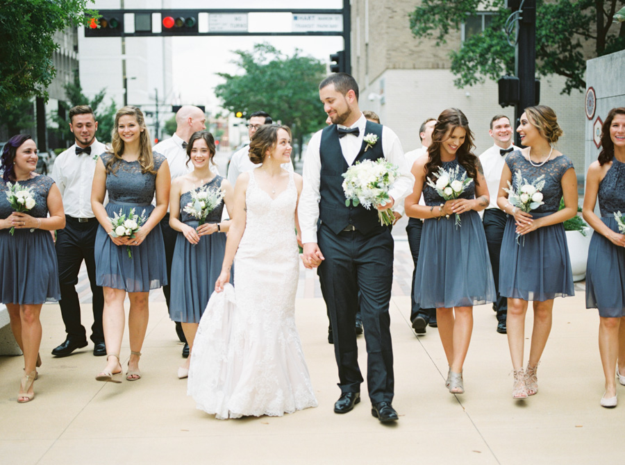 Outdoor Downtown Wedding Party Portrait with White Lace Trumpet Wedding Dress Mismatched Gray Short Bridesmaid Dresses and White and Greenery Bouquets   Downtown Tampa Wedding