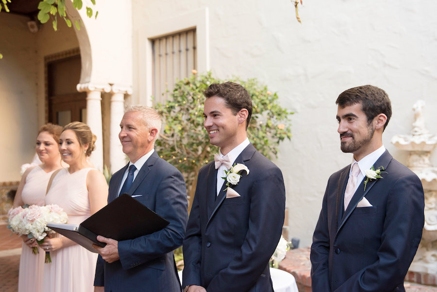 Groom's Reaction to Watching Bride Walk Down the Aisle | Ceremony Photo of Bridesmaids in Blush Alfred Sung Dresses and White and Blush Rose Bouquets and Boutonniere