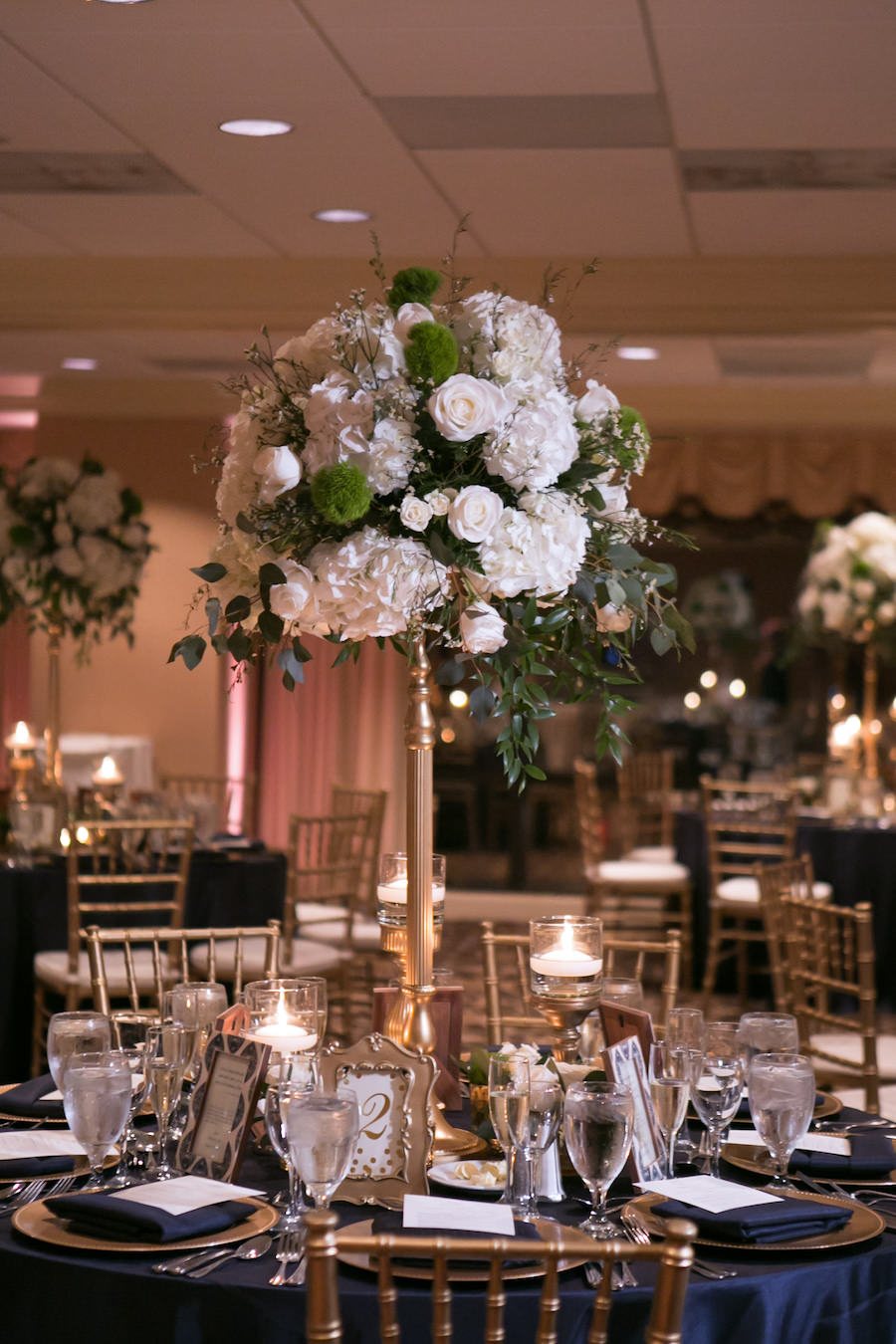 Classic Gold and Navy Wedding Reception Decor with Gold Chiavari Chairs and Tall White Rose, Hydrangea, and Greenery Centerpieces with Navy Blue Linens   Tampa Bay Wedding Venue The Tampa Club   Northside Florist