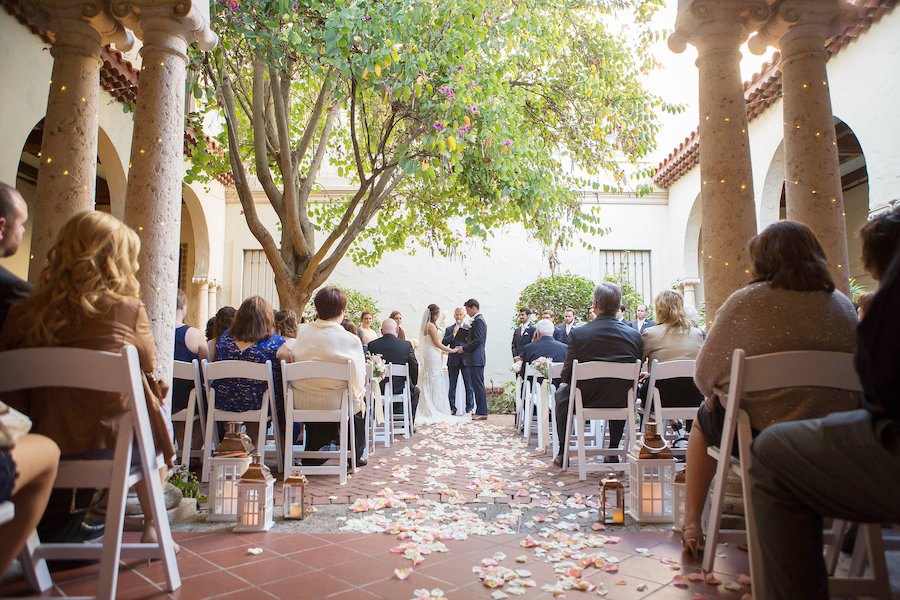 Wedding Ceremony Decor with Rose Petal Strewn Aisle with White and Gold Candle Holders and Folding Chairs at Modern Elegant Blush Wedding | Tampa Bay Photographer Kristen Marie Photography | St Petersburg Wedding Venue Museum of Fine Arts