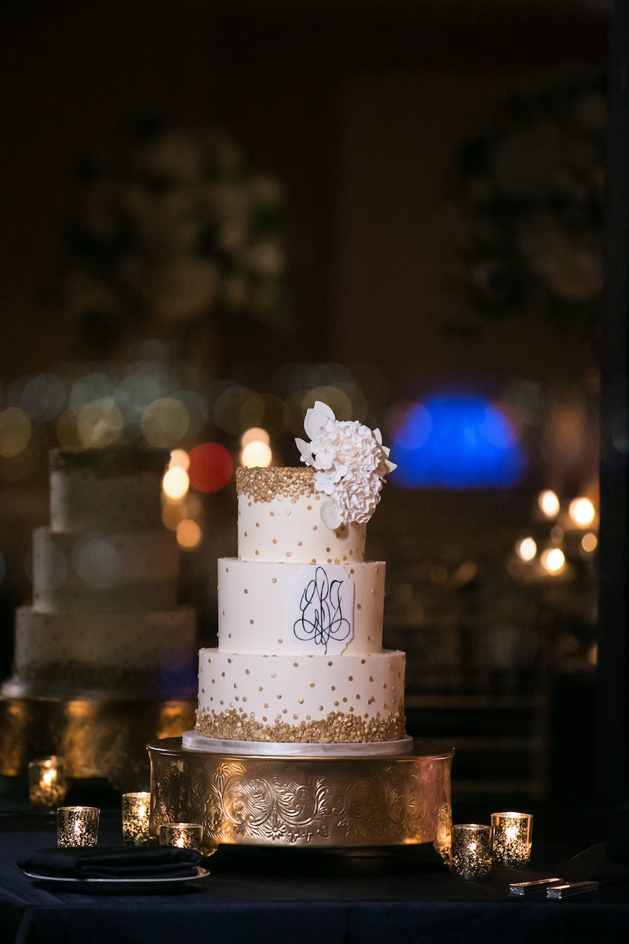 Three Tiered White and Gold Round Wedding Cake with White Floral Hydrangea Cake Topper at Classic Gold and Navy Wedding   Tampa Bay Cake Baker Hands on Sweets