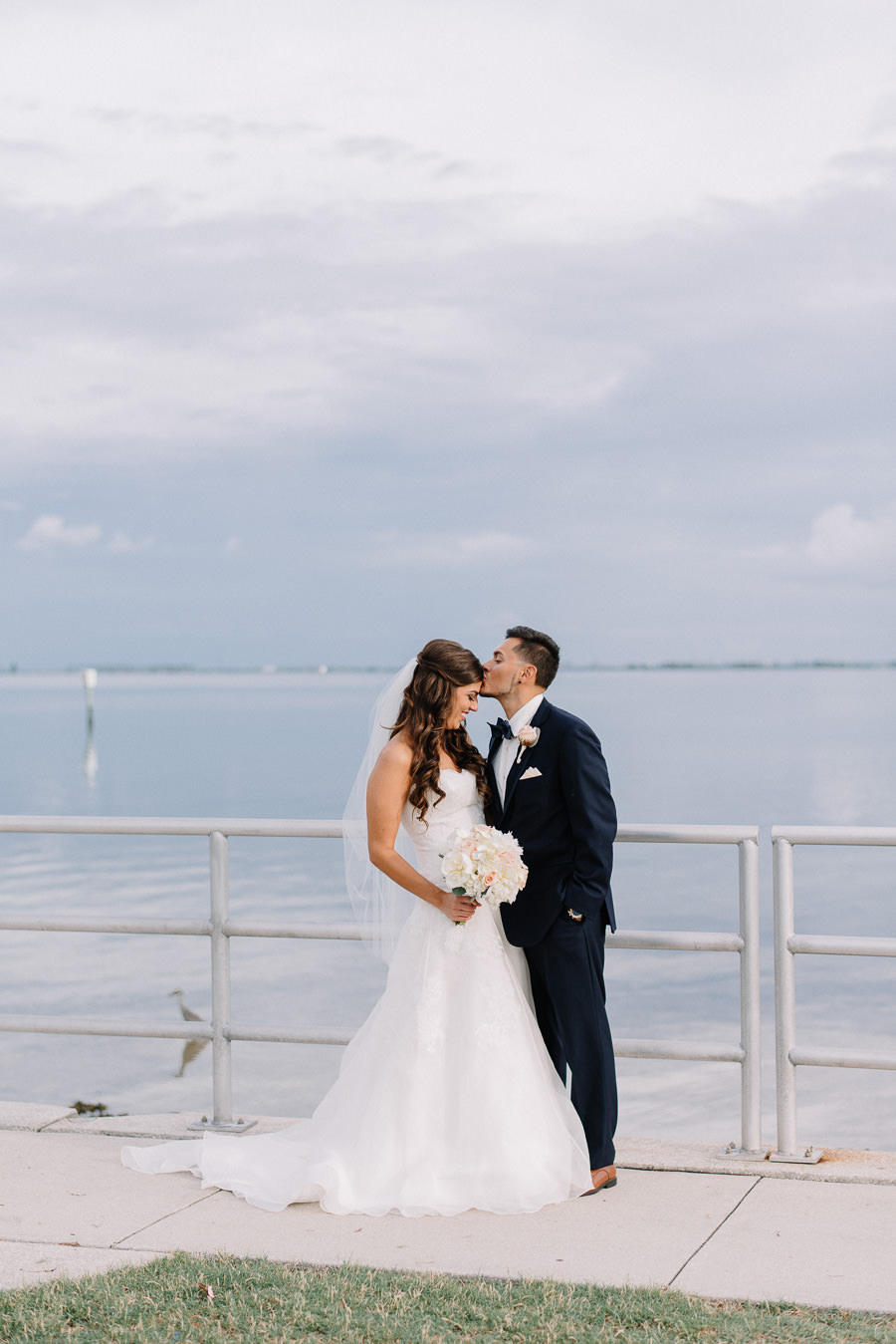 Outdoor Waterfront Wedding Couple Portrait with Watters Sweetheart Dress, Blush Rose Bouquet with Greenery, and Navy Suit at Tampa Bay Wedding Venue Safety Harbor Resort and Spa