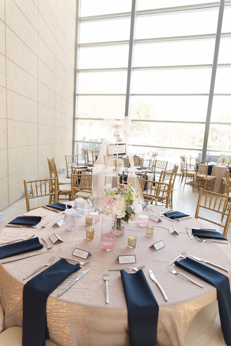 Modern Elegant Reception Table Decor with White Floral Centerpieces and Greenery, Blush Linens and Navy Blue Napkins, Silver Mercury Votive Candle Holders and Gold Chiavari Chairs