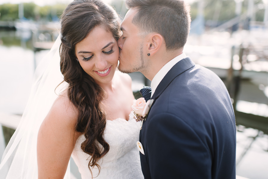 Outdoor Waterfront Wedding Couple Portrait with Lace Watters Sweetheart Dress, Blush Rose Boutonnière, and Navy Suit at Tampa Bay Wedding Venue Safety Harbor Resort and Spa
