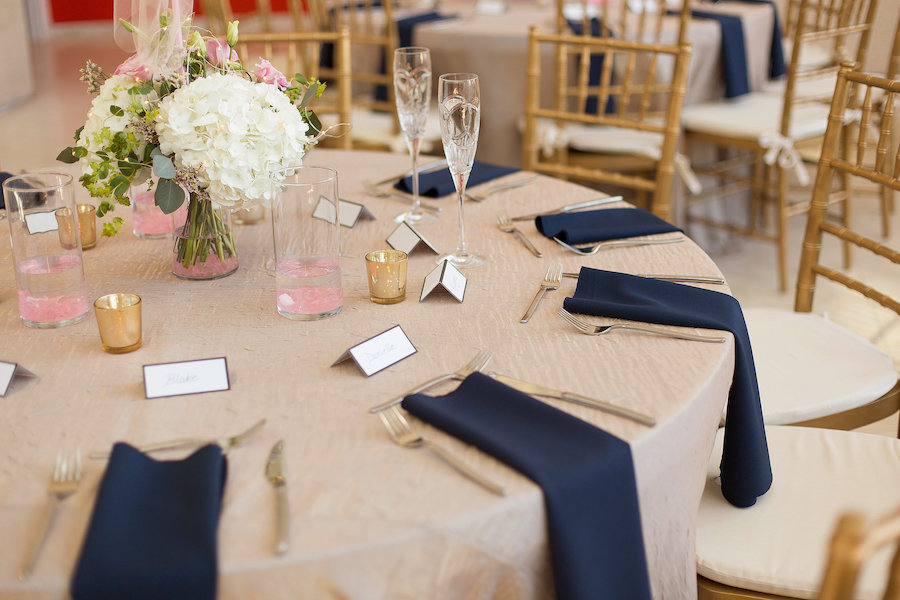 Modern Elegant Reception Table Decor with Low White Hydrangeas, Pink Roses, and Greenery Centerpieces and Blush Linen with Navy Blue Napkins, Gold Mercury Votive Candle Holders and Gold Chiavari Chairs
