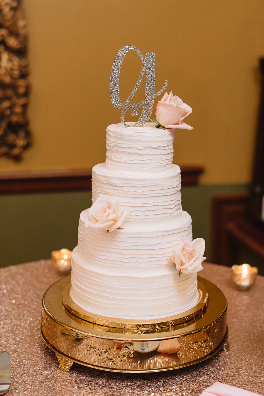 Elegant and Romantic 4-Tier Round Textured Wedding Cake from Tampa Bay Bakery A Piece of Cake on Gold Serving Platter with Blush Roses and Stylish Glitter Monogram Initial Topper