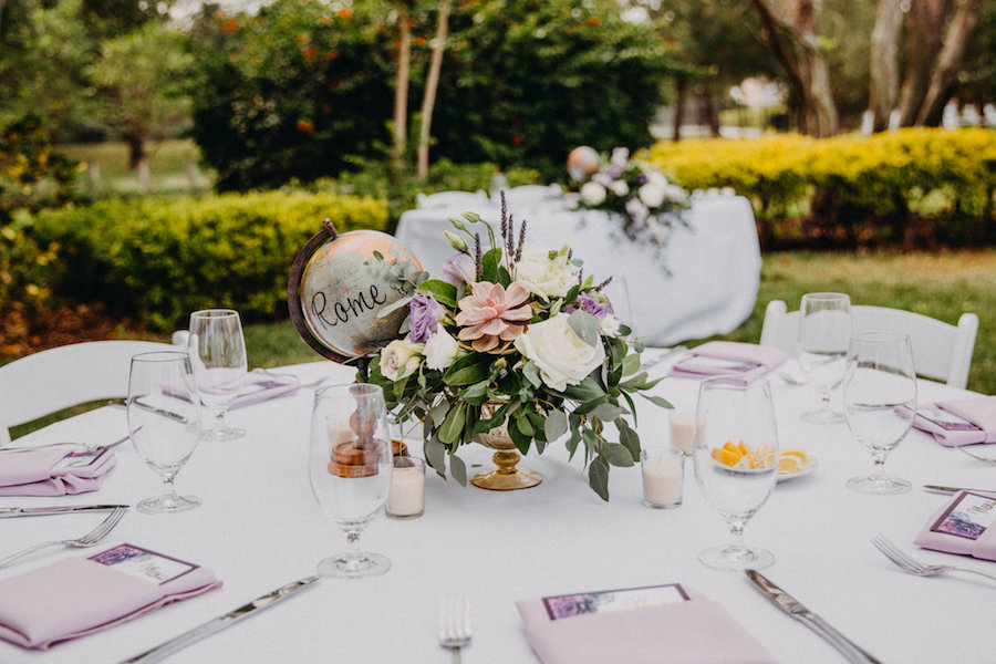 Outdoor Garden Wedding Reception Decor with Purple and White Flowers and Succulent Greenery Low Centerpiece in Gold Vase with Globe Table Number   Travel Themed Wedding Inspiration