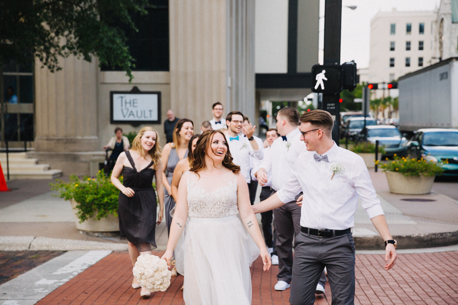 Downtown Tampa Wedding Party Portrait with Watters Wedding Dress, Round White Rose Bouquet, and Groom in White Shirt with Gray Pants and Blue Bowtie   Tampa Bay Wedding Venue The Vault