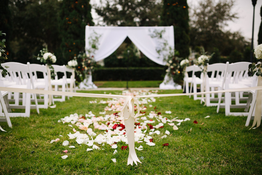 Ceremony Decor at Tampa Bay Garden Wedding Venue The Palmetto Club with White Fabric Arch, Climbing Greenery and Red Rose Bouquets, and White Folding Chairs with Rose Petal Aisle